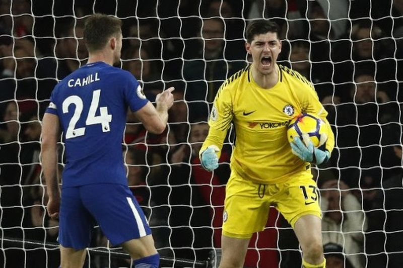 Chelsea's Belgian goalkeeper Thibaut Courtois (R) celebrates saving a shot with Chelsea's English defender Gary Cahill during the English Premier League football match between Arsenal and Chelsea at the Emirates Stadium in London on January 3, 2018.  / AFP PHOTO / Adrian DENNIS / RESTRICTED TO EDITORIAL USE. No use with unauthorized audio, video, data, fixture lists, club/league logos or 'live' services. Online in-match use limited to 75 images, no video emulation. No use in betting, games or single club/league/player publications.  /